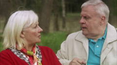 Senior couple arguing on a bench in the forest, Sweden. Stock Footage