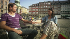 MS Young couple sitting at pavement caf_ / Copenhagen, Denmark, Scandinavian Stock Footage