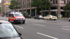 Ambulance speeding down road in Germany panned view Stock Footage