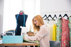 Woman using sewing machine Stock Photos