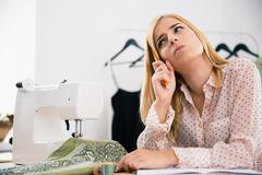 Female designer sitting at her workplace in workshop - stock photo