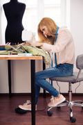 Female designer using sewing machine in workshop Stock Photos