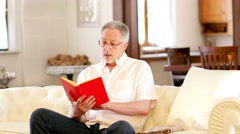 Mature man reading a book Stock Footage