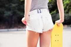 Stock Photo of Female ass in shorts with skateboards outdoors