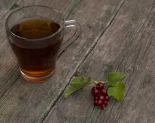 Stock Photo of the transparent cup of tea and currant on the shabby desktop