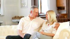 Couple talking and watching a tv program Stock Footage