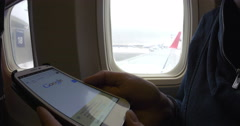 Internet surfing on cell phone before flight Stock Footage