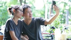 Happy asian man with girl friend using cell phone together ,are selfy - stock footage
