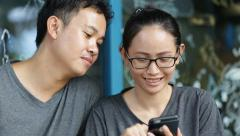 Happy asian man with girl friend using cell phone together ,are selfy Stock Footage