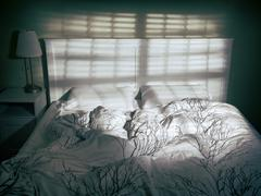 Unmade empty bed in dim light coming from a window through blinds Stock Photos