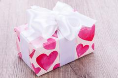 Pretty Valentines gift with hearts on the giftwrap - stock photo
