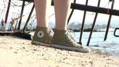 Legs of a young girl in sneakers is suitable to water. Converse All Stars - stock footage