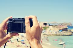 man taking a picture at Cala Conta beach in San Antonio, Ibiza Island, Spain - stock photo