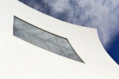White concave facade facade detail clouds reflected in the windows auditorium - stock photo