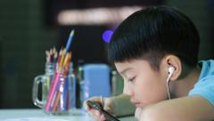 Asian boy in student uniform are painting on a white paper at home Stock Footage