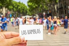 Stock Photo of closeup of the hand of a young man showing a signboard with the text Las Ramb