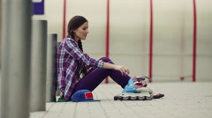 Woman is going rollerblading. Sitting on a bench in a park and putting on inline - stock footage