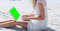Pretty blonde woman using laptop on beach Stock Footage