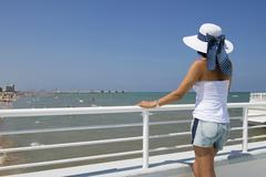 Woman with hat standing at railing on the beach Adriatic Senigallia Province of - stock photo