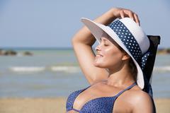 Woman with bikini and sun hat on the beach Adriatic Senigallia Province of - stock photo