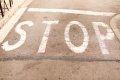 Stop painted on asphalt outdoor Stock Photos