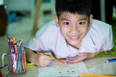 Asian child in student uniform painting on a white paper - stock photo