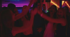 Friends toasting and holding beer high at a party on dance floor Stock Footage