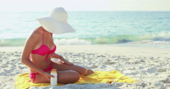 Pretty brunette taking care of her body putting on sun cream Stock Footage