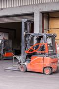 Stock Photo of Small orange forklift parked at a warehouse