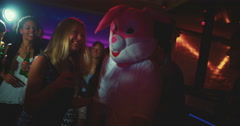 Guy as bunny at party club next young woman dancing Stock Footage