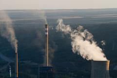 Chimneys of power plant coal production releasing smoke and steam. - stock photo