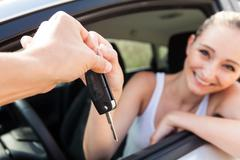 young smiling woman sitting in car taking key - stock photo