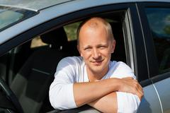 Excited driver holding the keys of his new car - stock photo