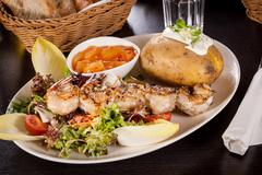 Stock Photo of Grilled prawns with endive salad and jacket potato