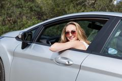 Young attractive happy woman sitting in car summertime Stock Photos