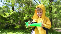 Stock Video Footage of Little boy in yellow raincoat plays with sprayer in summer park