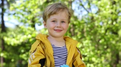 Little boy in yellow raincoat smiles and holds toys - stock footage