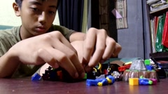 Big boy playing lego blocks Stock Footage