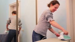 Housewife in gray blouse and jeans irons in room with mirror Stock Footage