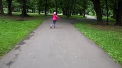 Back of girl in jeans roller-skates in summer green park Stock Footage