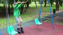 Boy teen with roller-skates play with swing in summer park Stock Footage