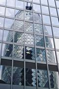 The Gherkin or 30 St Mary Axe building reflected in the glass of an adjacent Stock Photos