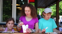 Mother and two children on roller skates eat in fast food cafe Stock Footage