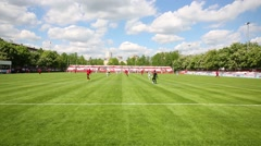 Football field with running players at summer day. View from net Stock Footage