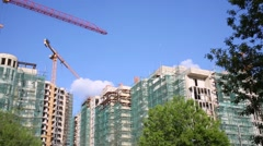 Cranes and building under construction at summer day Stock Footage
