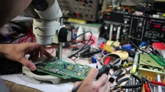 Man looks at motherboard through microscope and solders Stock Footage