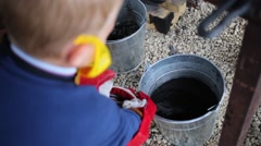 Child downs red-hot horseshoe to water in blacksmith workshop Stock Footage