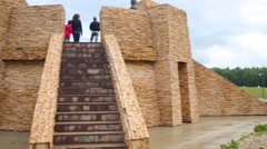 People stand on reconstructed wooden temple at green field Stock Footage