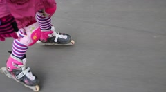 Legs of girl fast rolling skating on asphalt in park Stock Footage