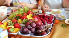 Plate with fresh raspberries, strawberries, grapes on table Stock Footage